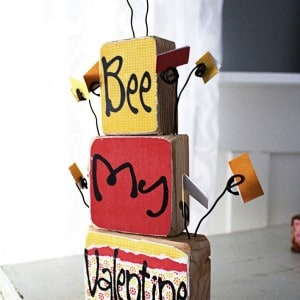 Leave sweet messages for your family with this DIY valentine display, built with scrap wood and decorated with pretty papers and Mod Podge.