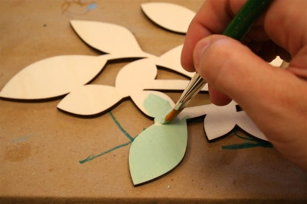 Painting a wood piece with light green craft paint using a paintbrush