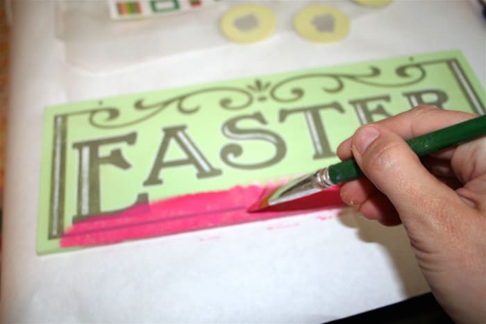 Paint edge of spring sign with acrylic paint