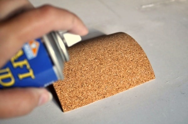 Spraying adhesive on a cork square
