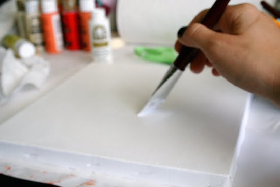 Painting a canvas with white acrylic paint