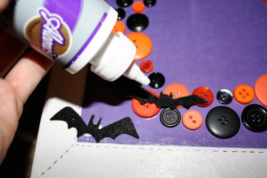 Gluing bats onto Halloween wall art