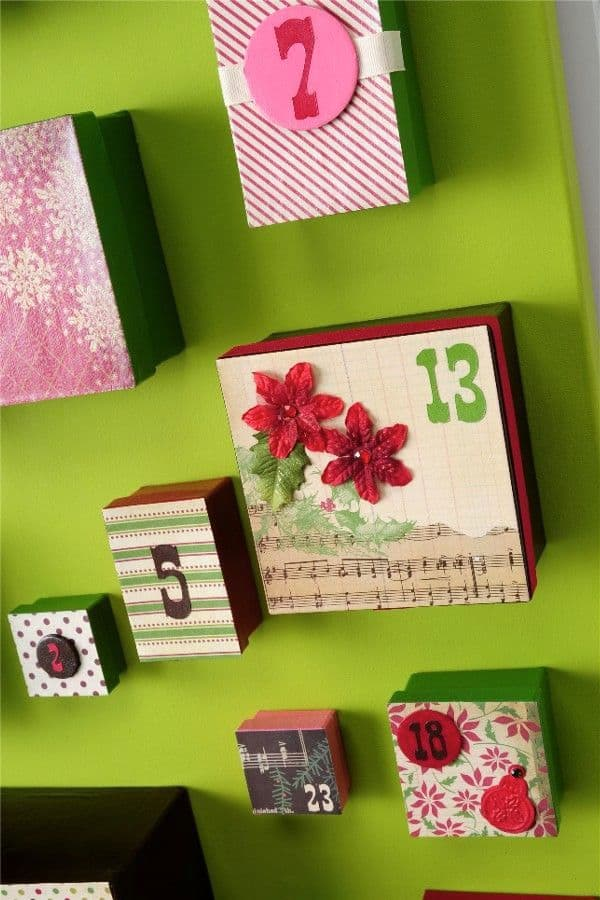 I wanted a DIY advent calendar that was going to make a huge statement, so I made this one using big boxes, a canvas, and my favorite holiday papers.