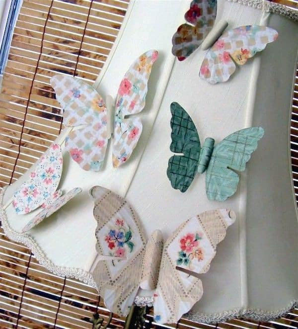 Turn antique metal butterflies into pretty magnets with wallpaper and Mod Podge. Use these easy butterfly decorations in your home decor!