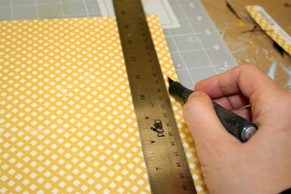 Trim a piece of scrapbook paper with a craft knife and metal ruler