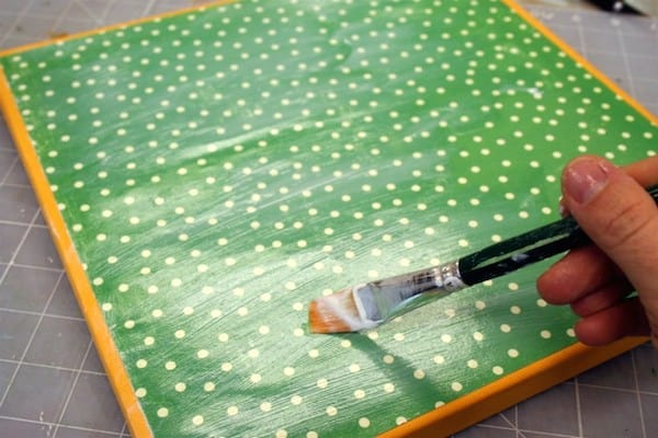 Attach scrapbook paper to a square canvas with Mod Podge