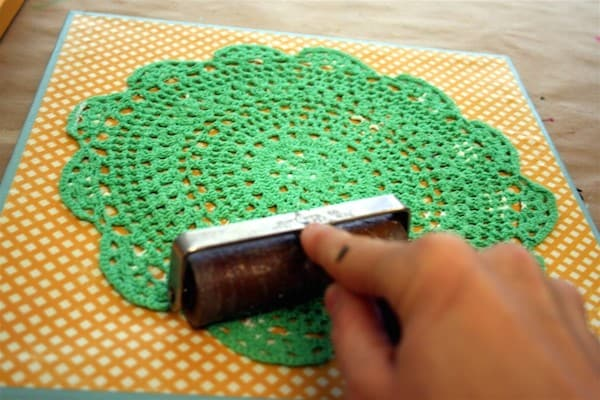 Roll out a doily on canvas with a brayer