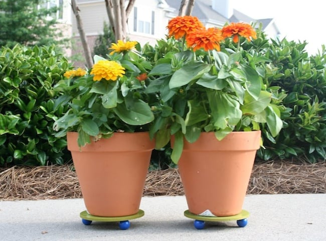 Make a DIY plant stand for spring or summer with this easy tutorial! Simply use paint, wood rings and wood balls from the craft store.