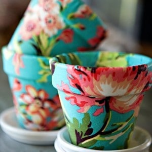 Decoupage fabric on terra cotta in this fun DIY flower pot project. You'll love the transformation from boring to fun and pretty!
