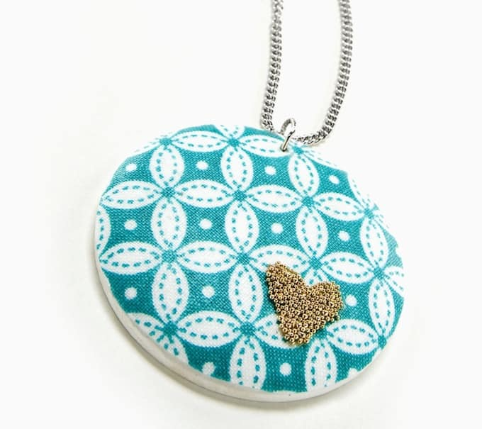 This beaded heart DIY necklace combines two unlikely colors - aqua and gold - with Mod Podge and microbeads for a unique jewelry look.