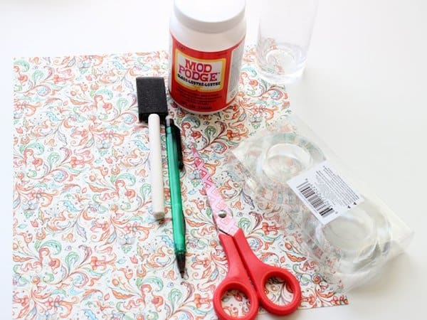 Scrapbook paper, Mod Podge gloss, glass candleholders from the dollar store, a foam brush, pencil, and scissors
