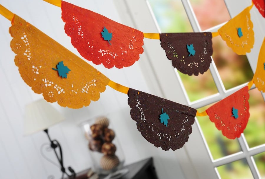 This DIY Thanksgiving banner is REALLY easy to make - just use paper doilies from the dollar store, paint, and Mod Podge!