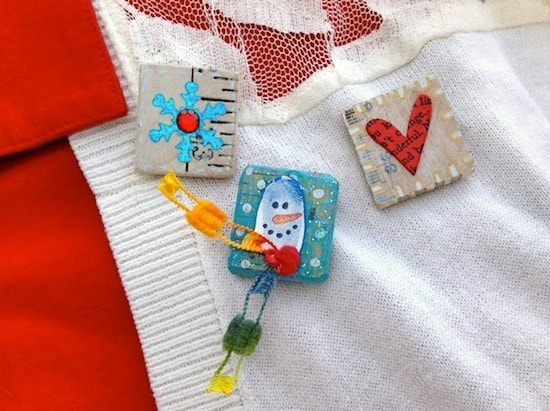 These simple snow pins are unique winter crafts for kids - use their finger prints, paint, and Mod Podge to make! SO EASY and cheap. They are great DIY gifts too. Toddlers and preschool age can participate. Learn to make with this tutorial.