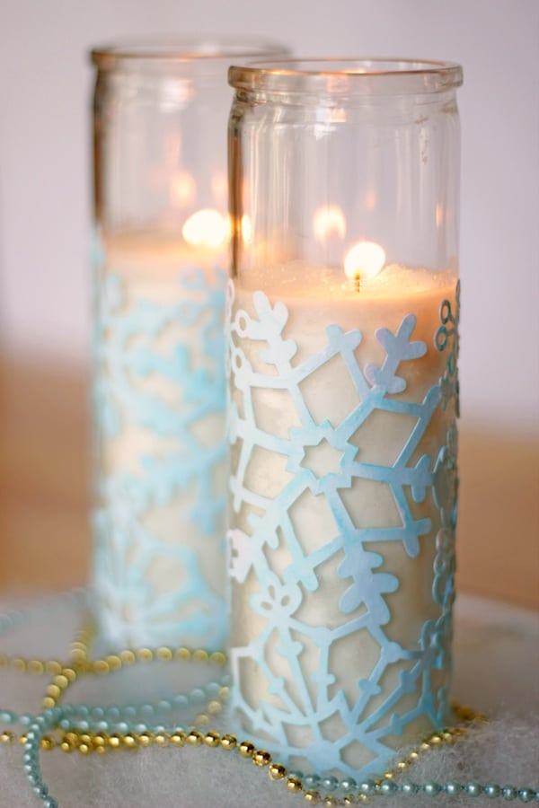 This snowflake craft is so easy and inexpensive! Use lasercut paper, food coloring and Mod Podge to decorate dollar store votives for cute winter decor.