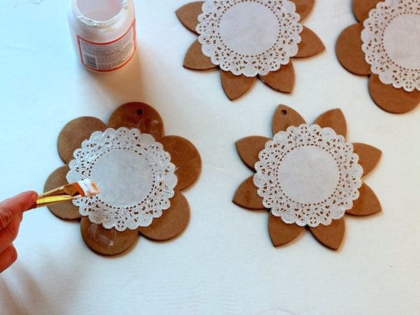 Using a brush to Mod Podge a doily to the top of a spring garland