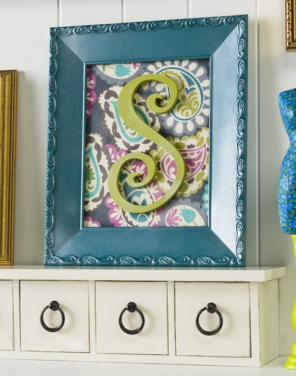 Create personalized initial wall art with an old budget frame, fabric and Mod Podge. I added Mod Podge Pearlized Sealer for an extra special touch.