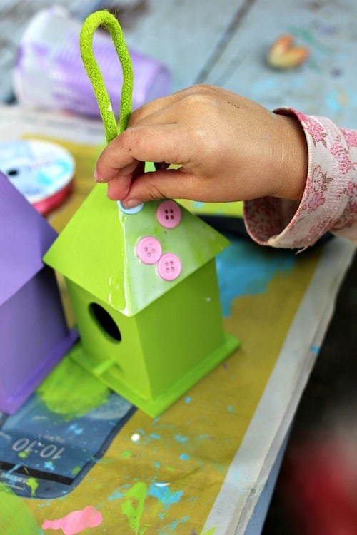 Glueing buttons onto the birdhouse with Mod Podge