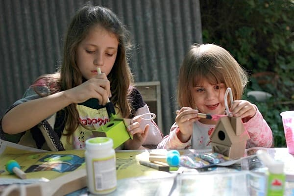 Two children painting birdhouses