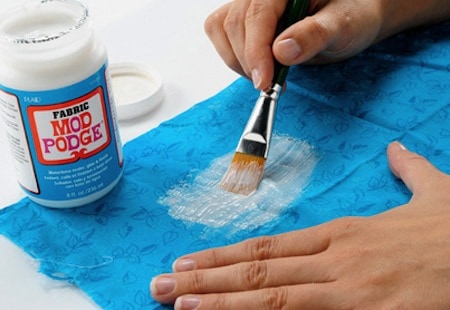 Spreading Fabric Mod Podge on a piece of fabric using a paint brush