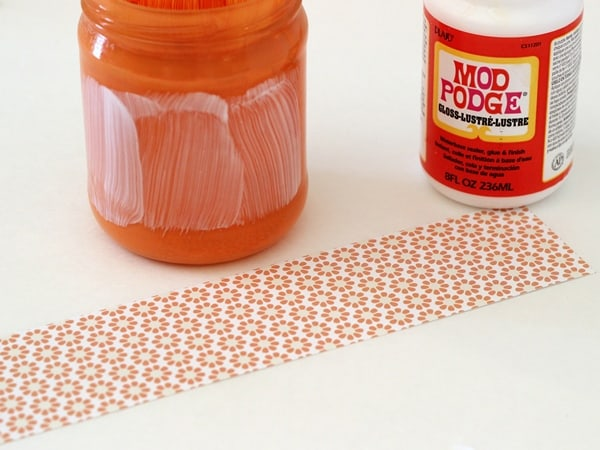 Applying Mod Podge to the outside of a glass jar