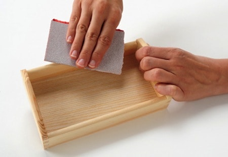 Sanding a small wood tray with a piece of sandpaper