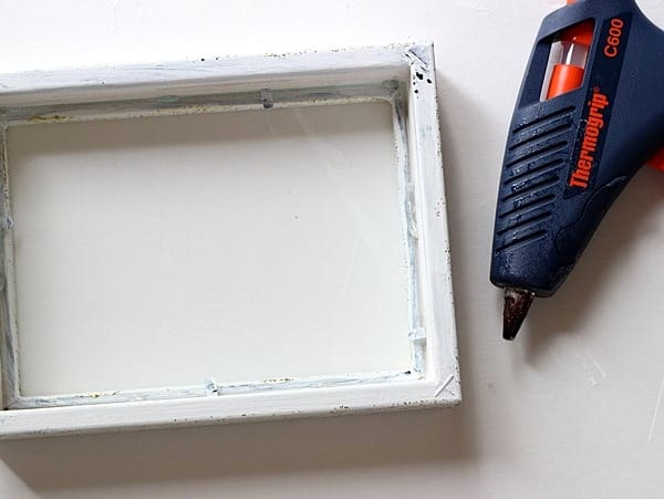 Hot glue the glass into the frame