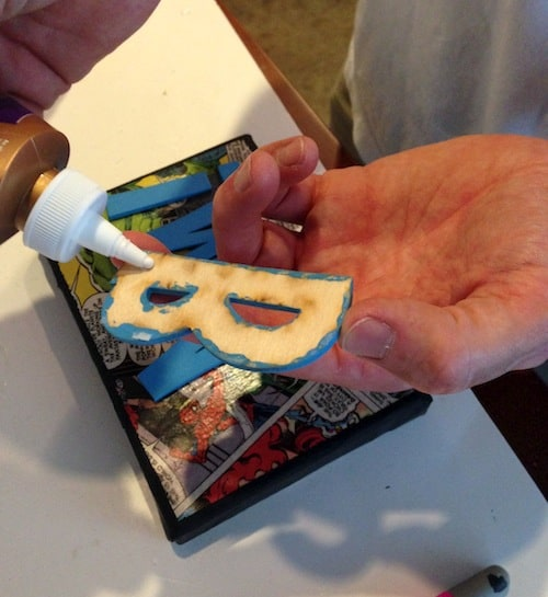 "Adding glue to the back of a painted wood letter ""B"""
