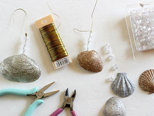 Make holiday decorations the easy way! This seashell ornaments DIY is so simple . . just use glitter and Mod Podge to make pretty Christmas decor.