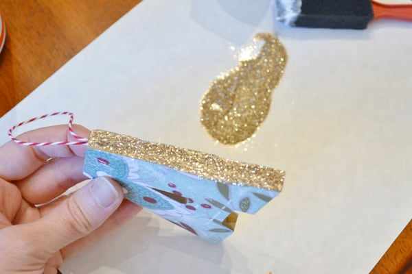 adding gold glitter to initial christmas ornaments