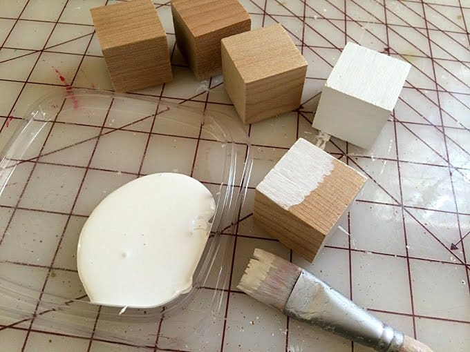 Painting wood blocks with white acrylic craft paint using a paintbrush