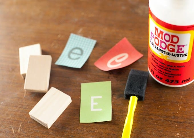 Small pieces of wood, letter cutouts, Mod Podge Gloss, and a paintbrush