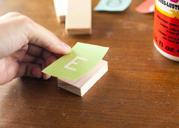 Placing a small rectangle with the letter E down on a wood block with Mod Podge
