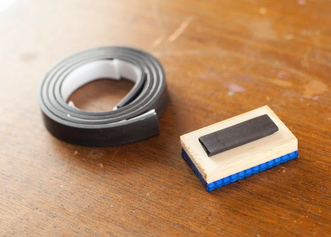 Roll of adhesive magnet laying next to a letter magnet