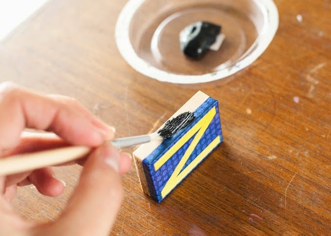 Painting the sides of the letter magnets with black paint