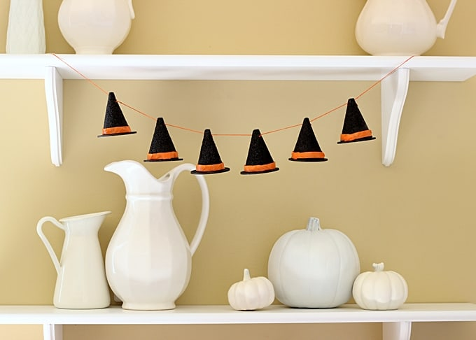 Use wood circles, foam cones and decoupage medium to make the cutest little DIY Halloween witch hat garland ever!