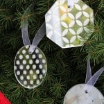 Use white glitter and Mod Podge Rocks stencils to make these pretty and simple DIY ornaments out of mirrors.