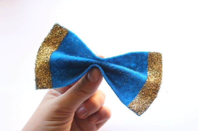 Two fingers pinching a felt bow