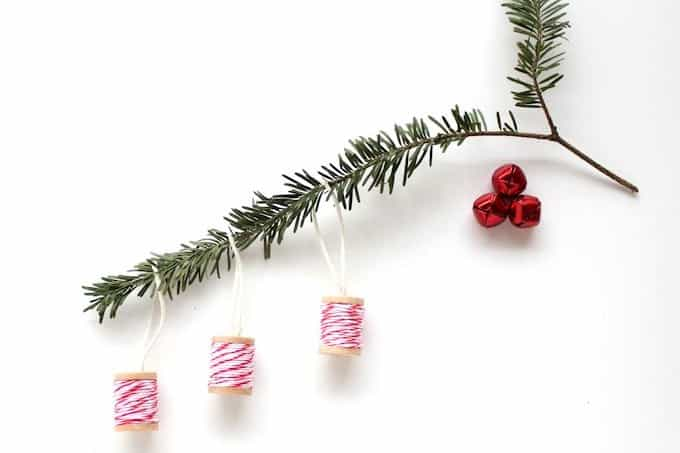 These thread spool DIY Christmas ornaments are as cute as can be, and are so easy to make with baker's twine and Mod Podge.