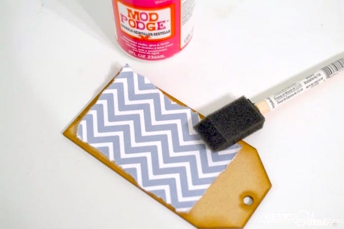 Applying Sparkle Mod Podge to a gift tag