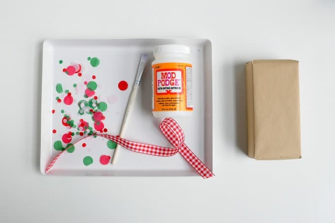 Confetti, wrapped gift, paintbrush, ribbon, and Mod Podge