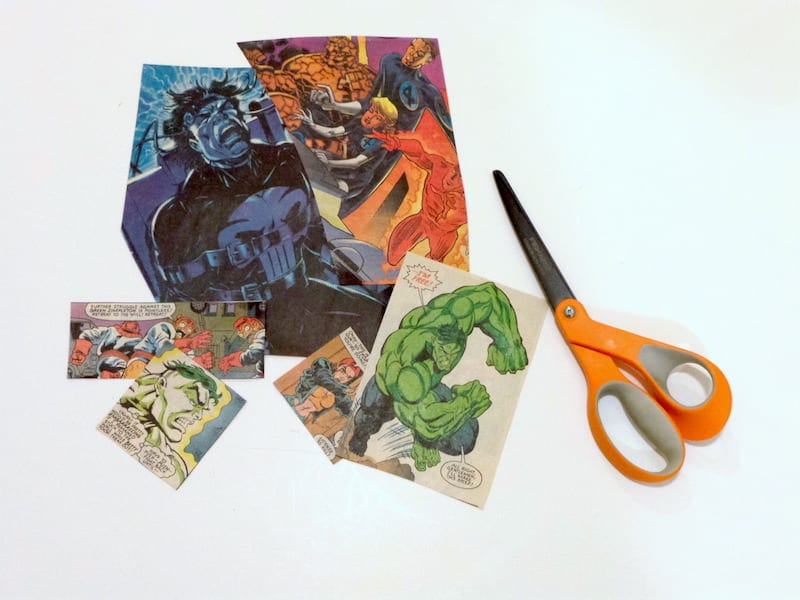 Comic book pages cut into smaller pieces and a pair of orange handled scissors