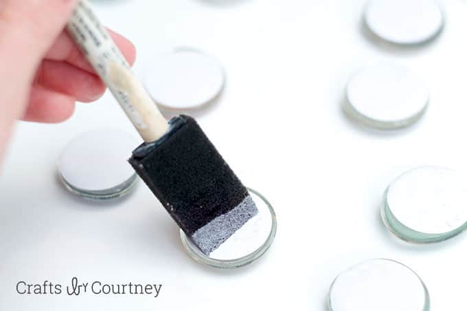 Painting Mod Podge on the back of marble magnets with a foam brush
