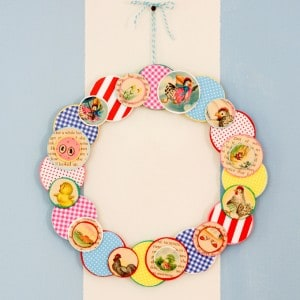 Make a simple DIY wreath for your craft room door using some of the pages from an old book, wood circles, and an embroidery hoop. So fun and colorful!
