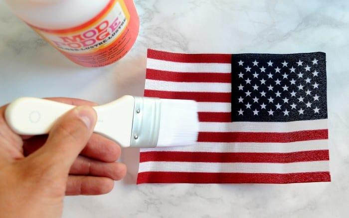 Applying Mod Podge to the back of a flag