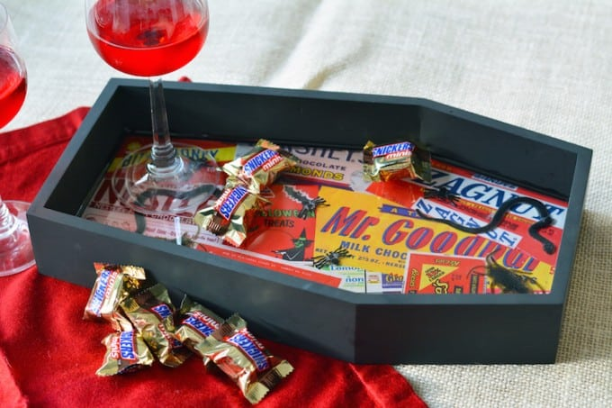 Turn a plain wood coffin decoration into a DIY Halloween tray covered with creepy crawlies! Perfect for surprising guests when they grab a piece of candy.