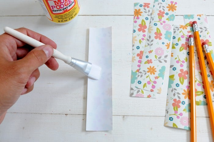 Painting Mod Podge Matte on the back side of a piece of paper with a white paintbrush