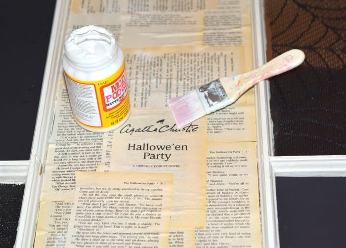 Painting Mod Podge on a book pages on a window pane