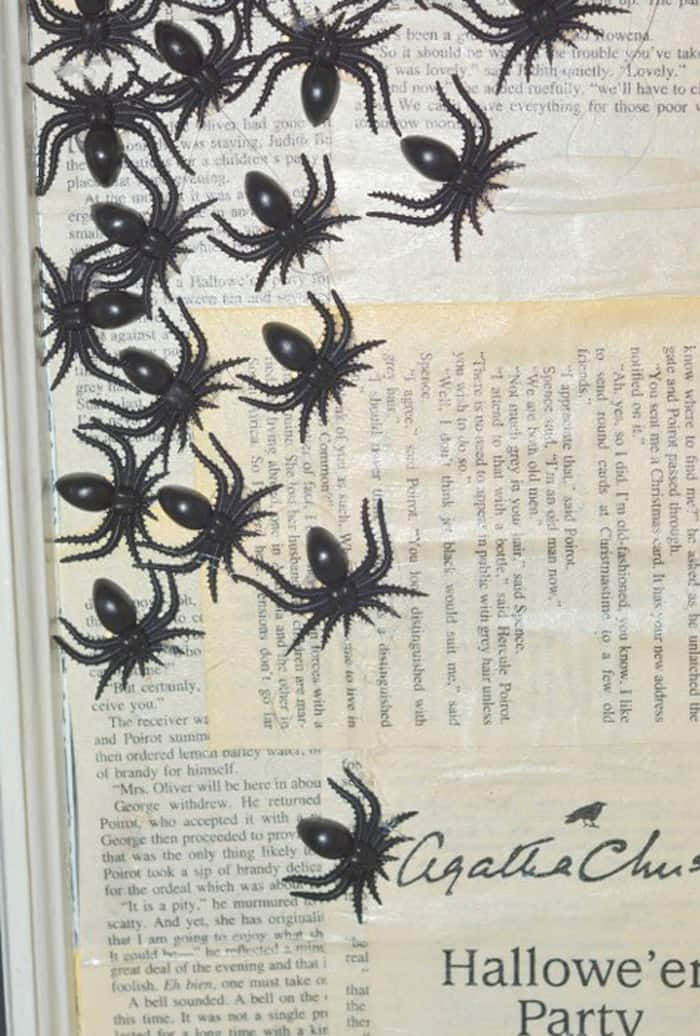 Plastic spiders glued to book pages on a Halloween window