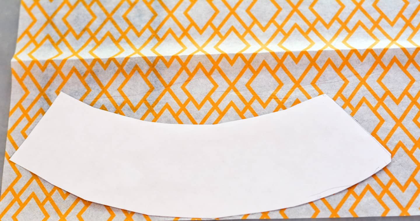 A paper pattern laid on the top of a piece of orange patterned tissue paper