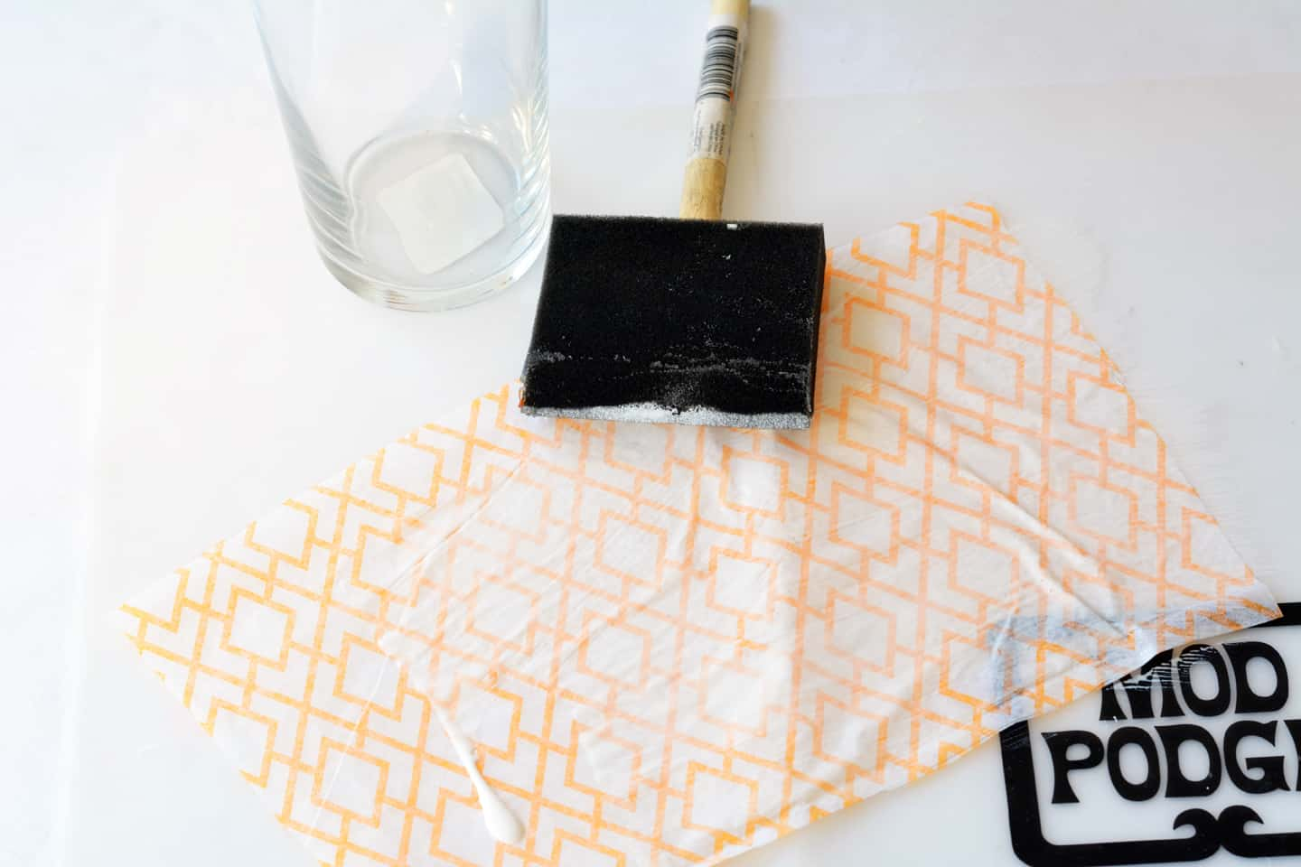 Add Mod Podge to tissue paper with a foam brush